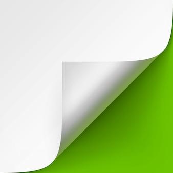 Gekrulde hoek van wit papier met schaduw close-up op helder groene achtergrond