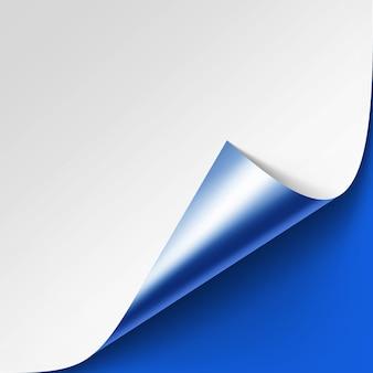 Gekrulde metalen zilveren hoek van wit papier met schaduw close-up op heldere blauwe achtergrond
