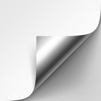 Gekrulde zilveren metalen hoek van wit papier met schaduw close-up geïsoleerd op grijze achtergrond
