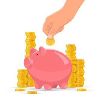 Geld besparen concept. roze spaarvarken met gouden muntstukkenstapels op achtergrond. menselijke hand zet munt