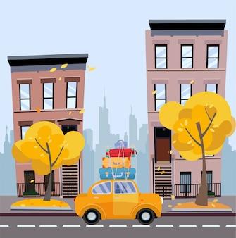 Gele auto met koffers op het dak tegen achtergrond van de herfstcityscape