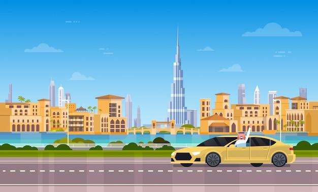 Gele taxiauto op weg over de stad van doubai
