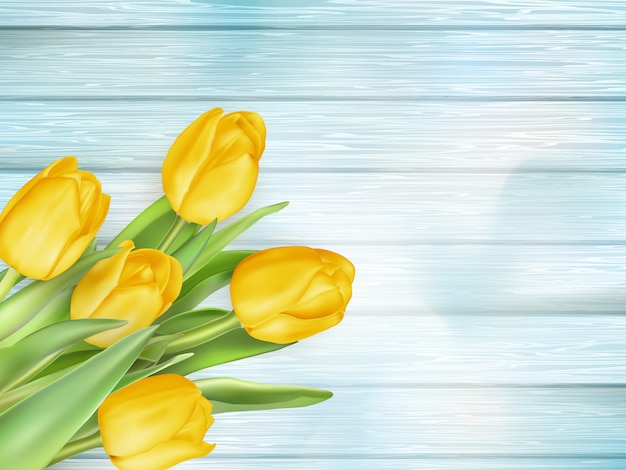 Gele tulpenbloemen op houten planken.