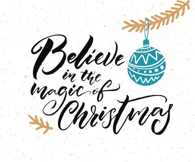 Geloof in de magie van kerstmis. kalligrafiebijschrift voor wenskaarten en cadeaulabels. hand getekende illustratie van kerstboomtak met blauwe bal.
