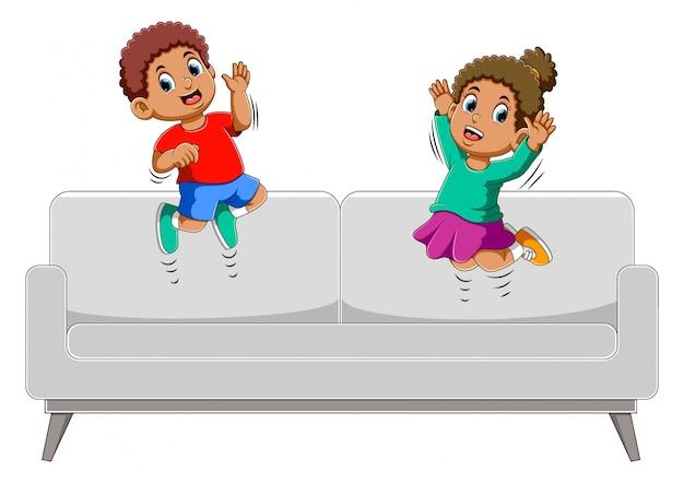 Gelukkig jongen en meisje springen op de sofa