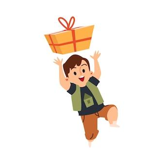 Gelukkig kind met een geschenkdoos klein kind springen van hoy van het krijgen van een cadeautje
