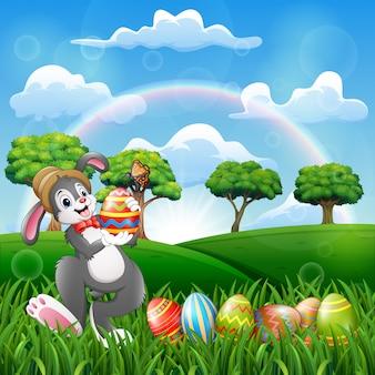 Gelukkig konijntje die een verfraaid paasei houden