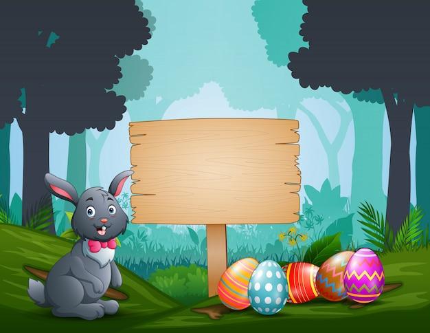 Gelukkig konijntje met paaseieren door een houten tekenraad
