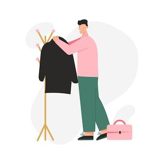 Gelukkig man hangt zijn jas op bovenkleding rek.