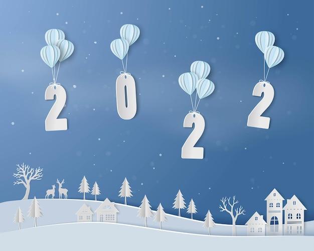 Gelukkig nieuwjaar 2022 met ballon zwevend boven het platteland op papier kunst achtergrond
