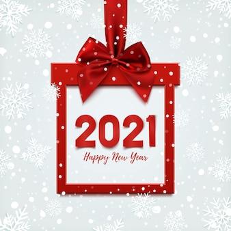 Gelukkig nieuwjaar, vierkante banner in de vorm van kerstcadeau met rood lint en boog, op winter achtergrond met sneeuw.