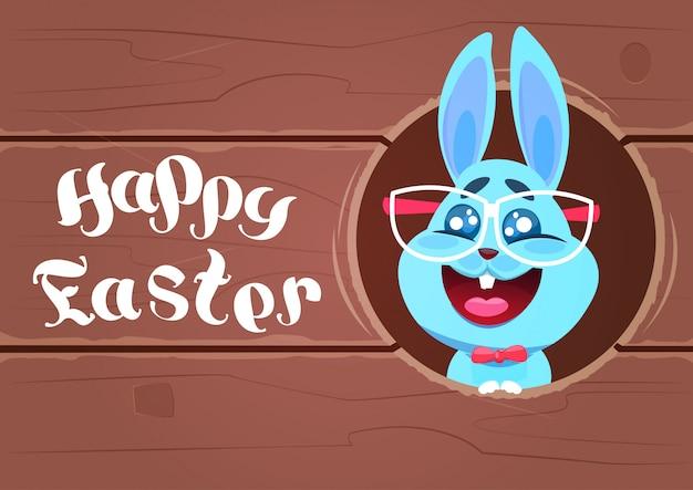 Gelukkig pasen-kaartontwerp met grappig konijn in glazen over houten geweven achtergrond