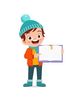 Gelukkig schattig klein kind studeren en dragen jas in winterseizoen