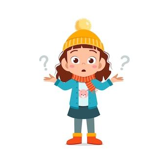 Gelukkig schattig klein voelt zich verward en draagt een jas in het winterseizoen