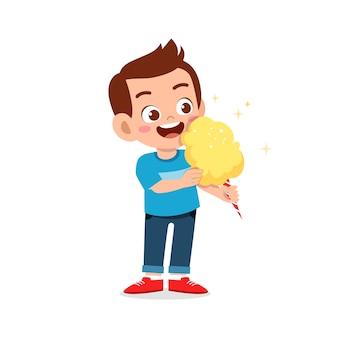 Gelukkig schattige kleine jongen jongen eet snoep en snoep