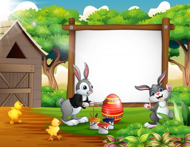Gelukkig schilderij ei met konijnen en kuiken op de boerderij