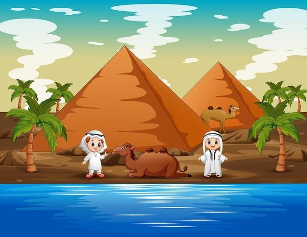 Gelukkige arabische jongens met kamelen in de woestijn