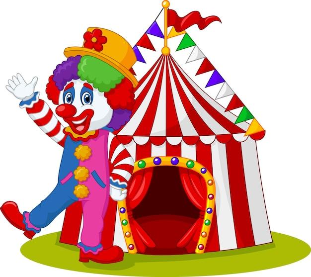 Gelukkige clown die met circustent op geïsoleerde achtergrond golft
