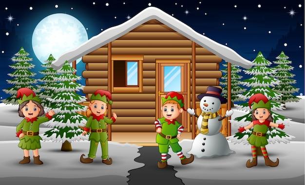 Gelukkige elfgroep die zich voor het sneeuwende huis bevindt