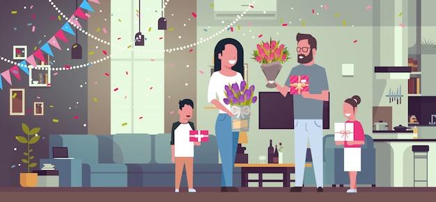 Gelukkige familie feliciteren met vrouw dag 8 maart met presenteert en bloemen in de woonkamer