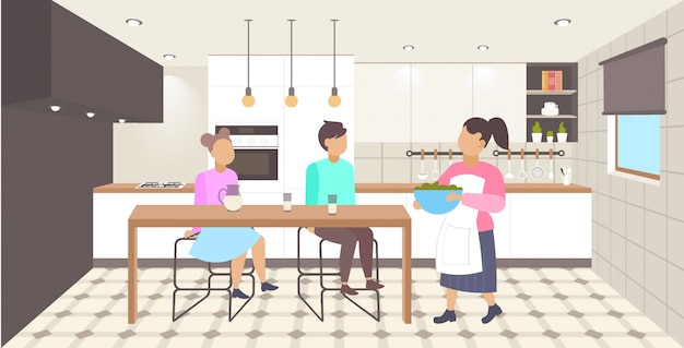 Gelukkige familie ontbijten moeder eten serveren aan haar zoon en dochter aan eettafel moderne keuken interieur cartoon tekens volledige lengte horizontale afbeelding