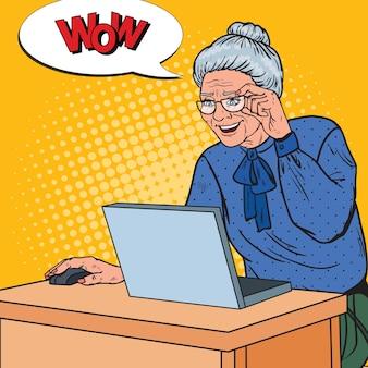 Gelukkige hogere vrouw die laptop met behulp van