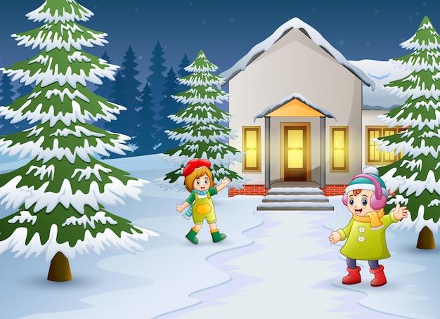 Gelukkige jonge geitjes die voor het sneeuwende huis spelen