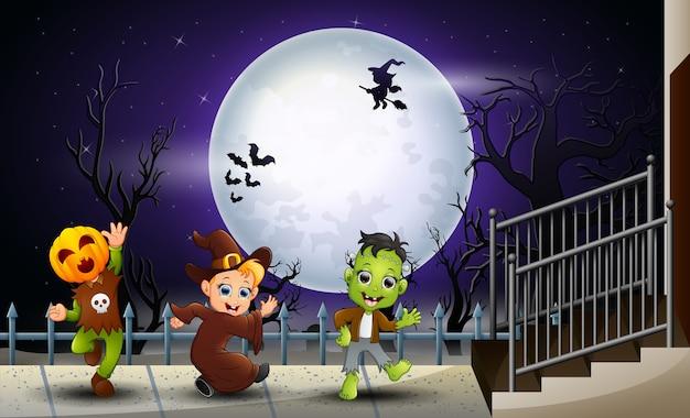 Gelukkige jonge geitjes halloween op de volle maanachtergrond