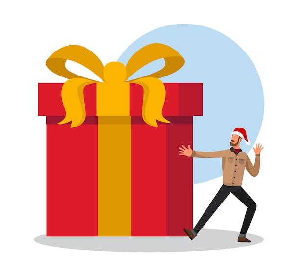 Gelukkige jonge mens die een hoed van de kerstman draagt die zijn grote aanwezige kerstmis toont
