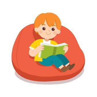 Gelukkige jongen die een boek leest, zittend op de bank in de kamer