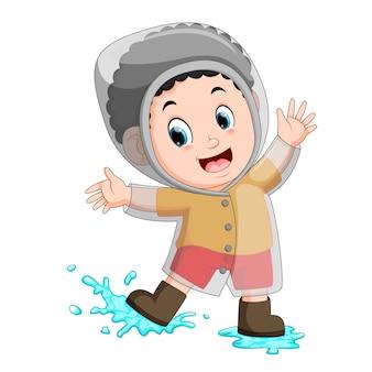 Gelukkige jongen die regenjas draagt
