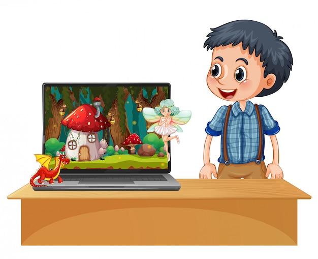 Gelukkige jongen naast laptop met magisch land op desktopachtergrond