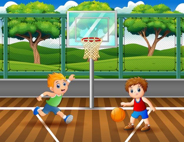 Gelukkige jongens spelen basketbal aan het hof