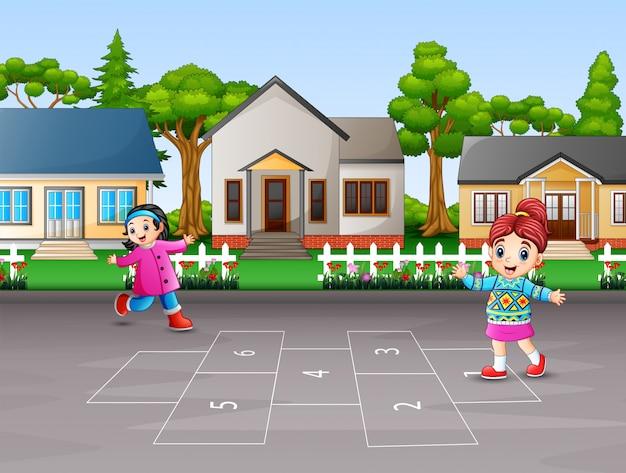 Gelukkige kinderen die hinkelspels in de werf spelen