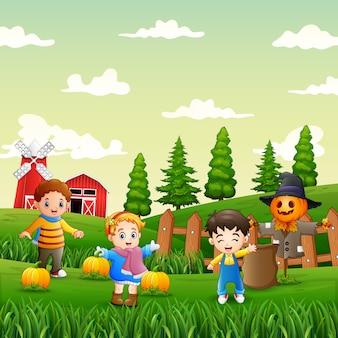 Gelukkige kinderen die pompoenen in de tuin oogsten