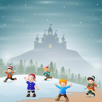 Gelukkige kinderen spelen in het besneeuwde landschap