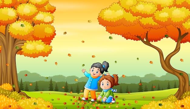 Gelukkige kinderen spelen met gevallen bladeren
