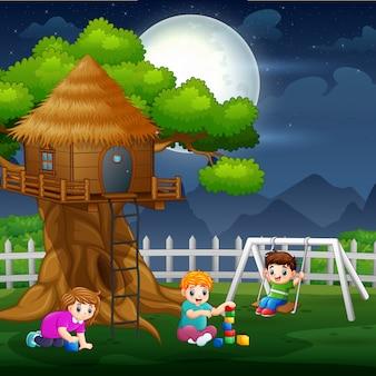Gelukkige kinderen spelen rond boomhut 's nachts