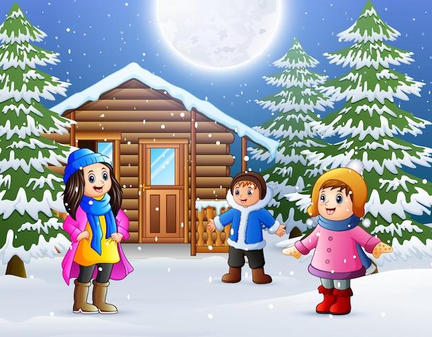 Gelukkige kinderen spelen voor een besneeuwde houten huis