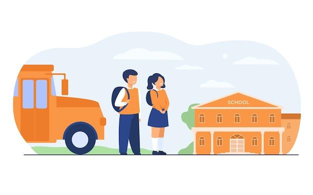 Gelukkige kinderen wachten schoolbus geïsoleerde platte vectorillustratie. cartoon meisje en jongen permanent op weg in de buurt van schoolgebouw.