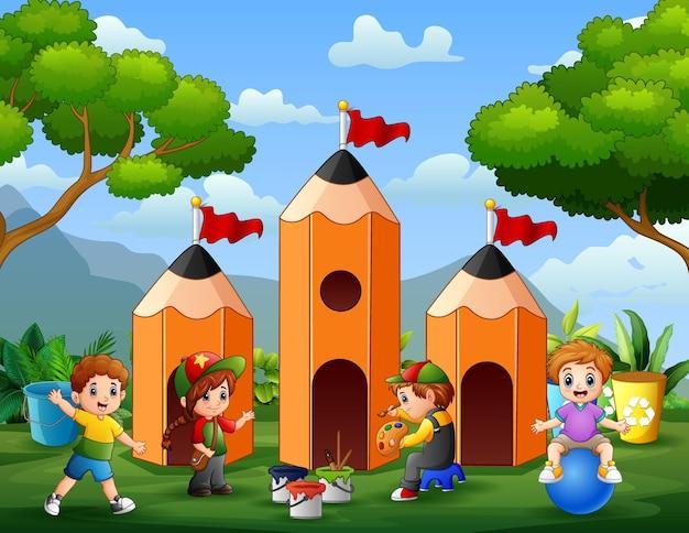 Gelukkige kleine studenten die met potloodhuis spelen