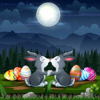 Gelukkige konijntjes die met paaseieren kussen in pasen-vooravond