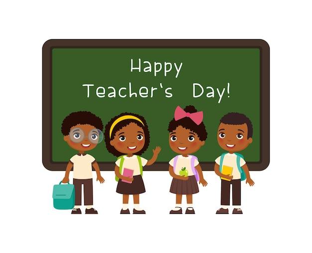 Gelukkige lerarendaggroet glimlachende afrikaanse leerlingen die zich dichtbij bord in klaslokaal bevinden