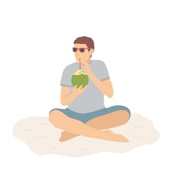 Gelukkige man in korte broek op zandstrand drinkt een kokoscocktail en ontspant