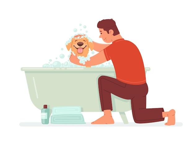 Gelukkige man wast de hond in de badkamer de man zorgt voor zijn huisdier hygiëne huisdier