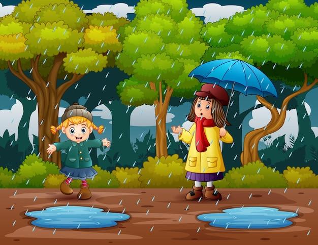 Gelukkige meisjes die in de regen spelen