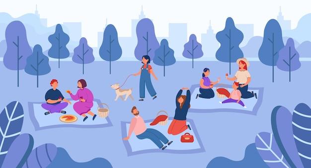 Gelukkige mensen die tijd doorbrengen met picknicken in de buitenlucht