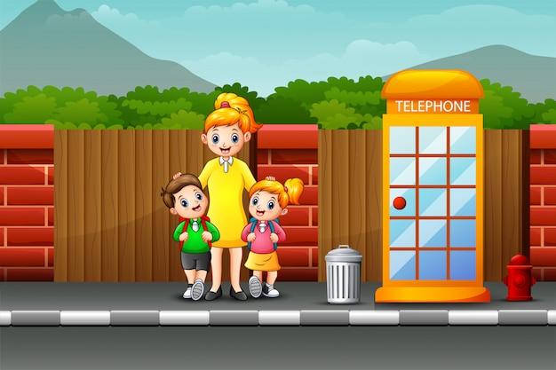 Gelukkige moeder en kinderen die zich op de kant van de weg bevinden