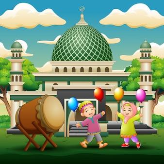 Gelukkige moslimjonge geitjes die ballons voor de moskee houden
