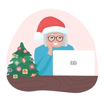 Gelukkige oma met kerstmuts die naar laptop kijkt oude vrouw met een bril die online spreekt